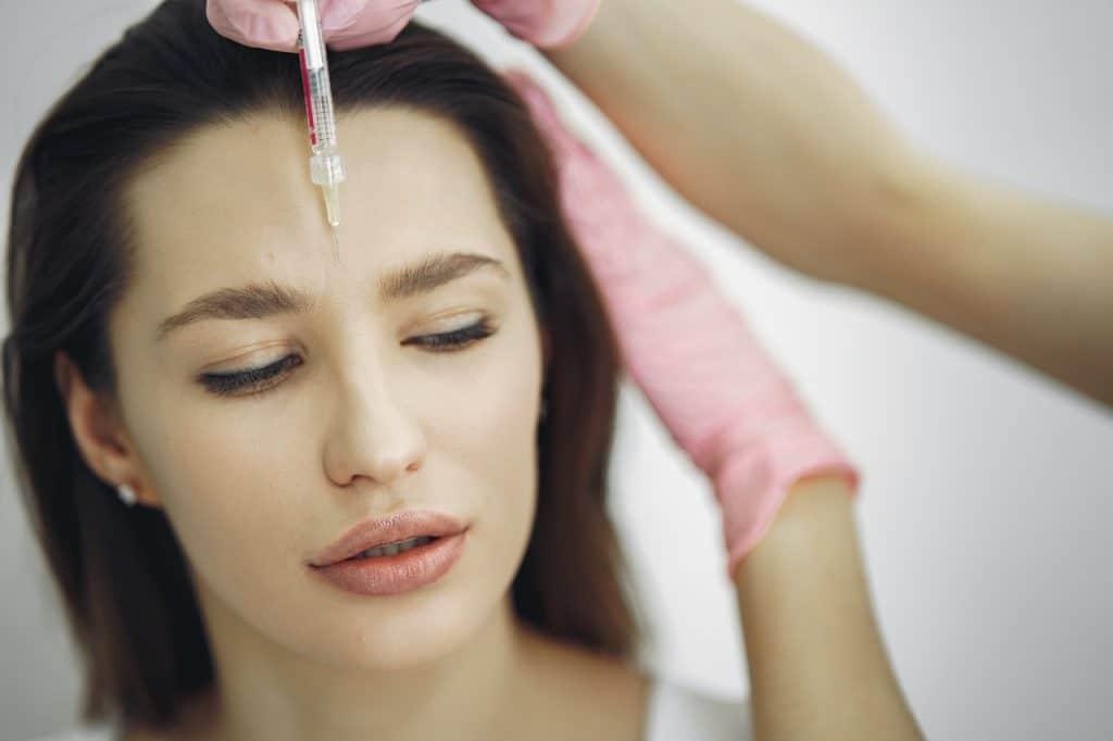 jeune femme qui fait des injections dans un cabinet de médecine esthétique